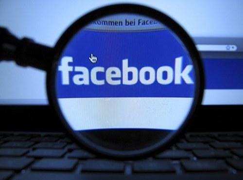 Facebook-Logo auf dem Bildschirm durch eine Lupe betrachtet