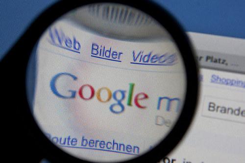 Google-Logo auf dem Bildschirm durch eine Lupe betrachtet