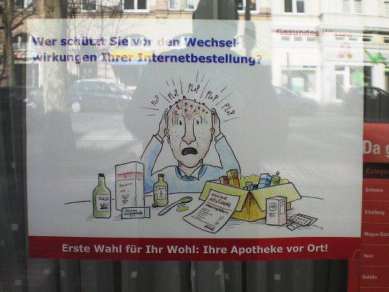 Außenwerbung im Schaufenster einer Apotheke: Ein Mann hat ein Paket voller Medikamente ausgepackt und offenbar einen Löffel einer Zubereitung genommen, auf seinem Kopf ploppen lauter rote Pickel auf. Dazu der vorsätzlich angstausbreitende Text: Wer schützt sie vor den Wechselwirkungen Ihrer Internetbestellung? -- Gesundes Wissen. Apotheke -- Erste Wahl für Ihr Wohl: Ihre Apotheke vor Ort!